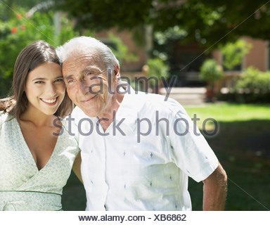 Senior man standing outdoors with arm around woman smiling - Stock Photo