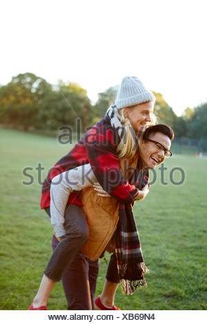 Man giving girlfriend a piggyback in park - Stock Photo