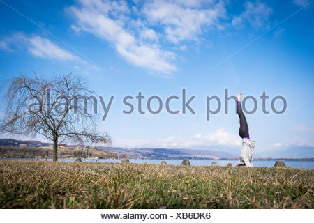Woman practicing yoga doing a headstand at a lake - Stock Photo