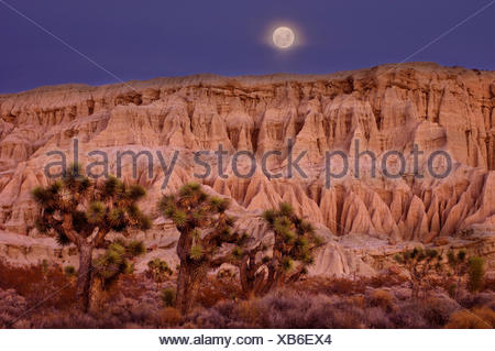 Full moon setting over Badlands at Red Rock Canyon State Park,Dawn,California,United States of America - Stock Photo