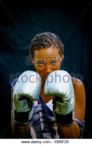 Portrait of woman wearing boxing gloves looking at camera - Stock Photo