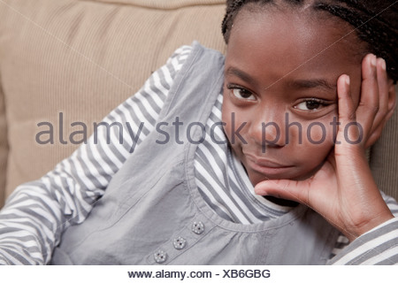 Young girl relaxing on couch, Illovo Family, Johannesburg, South Africa. - Stock Photo