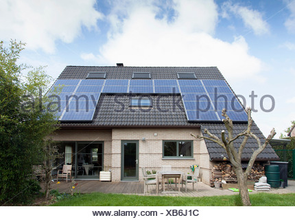 Detached bungalow with solar panels on roof - Stock Photo