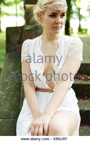 young woman in white lace dress sitting on stairs in the forest - Stock Photo