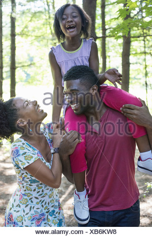 A family two parents and a child sitting on her father's shoulders - Stock Photo