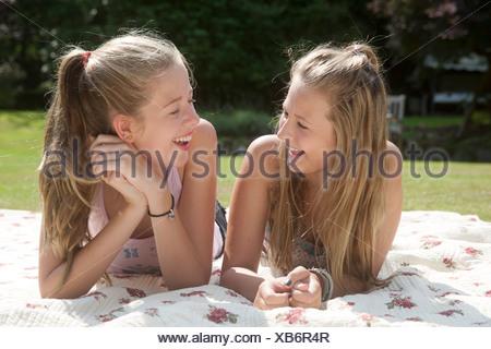 Two teenage girls lying on picnic blanket - Stock Photo