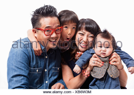 Studio portrait of mid adult couple with daughter and baby boy - Stock Photo