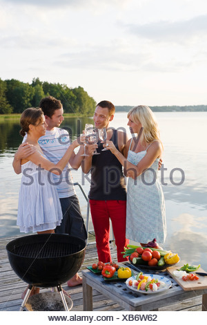 Four people standing on jetty and toasting with glasses - Stock Photo