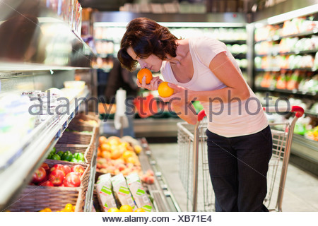 Woman smelling fruit at grocery store - Stock Photo