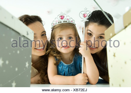 Little girl with mother and sister, dressed as princess, birthday gifts in foreground - Stock Photo