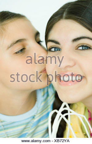 Two young female friends, one kissing the other on the cheek - Stock Photo