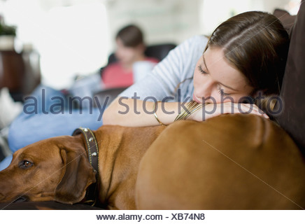 Woman laying on sofa with dog - Stock Photo