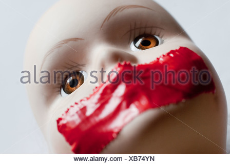Close up of face of girl doll with red tape on mouth - Stock Photo