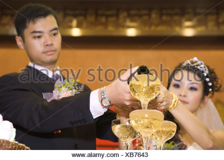 Bride and groom pouring champagne into stacked champagne glasses together - Stock Photo