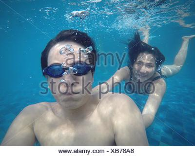 Man With Smiling Woman Swimming In Pool - Stock Photo