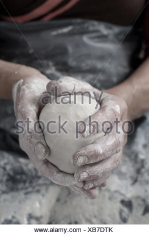 Close-up of female potter's hand holding clay, Bavaria, Germany - Stock Photo