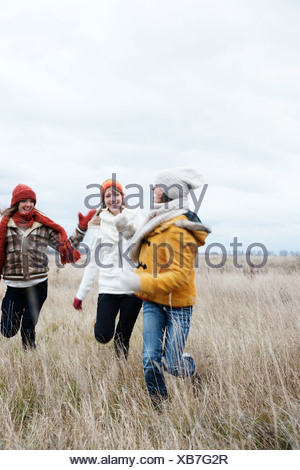 Three laughing teenage girls wearing hats and scarfs - Stock Photo