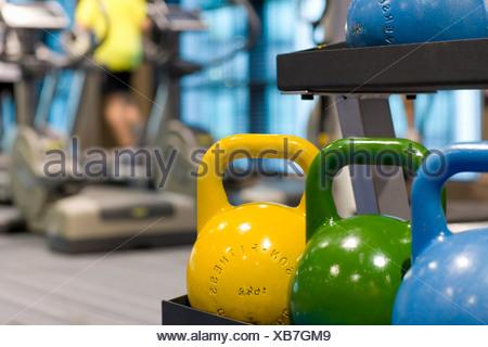 Colorful medicine balls on rack in health club - Stock Photo