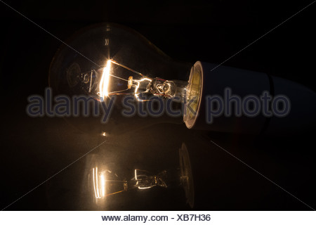 Light bulb without glass turned over on black background - Stock Photo