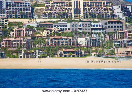 View from the ocean of the colorful houses, resorts, and apartments on the beach of Cabo San Lucas. You can see on the beach set on the sand a couple - Stock Photo