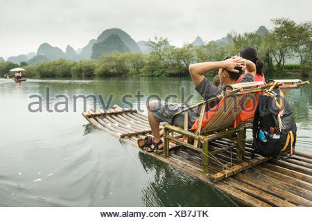 A family tours the Li River on a bamboo raft. - Stock Photo