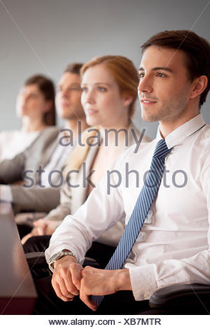 Young business professionals attending conference - Stock Photo