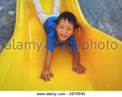 Portrait Of Happy Girl Playing On Yellow Slide In Playground - Stock Photo