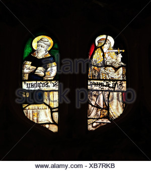 Medieval stained glass, St. Agnes with dagger at her neck, holding a lamb, St. Stephen holding stones of martyrdom, Sandringham - Stock Photo