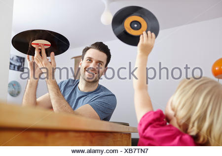 Father showing old vinyl records to daughter - Stock Photo