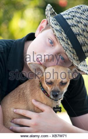 young boy holding his pet Chihuahua - Stock Photo