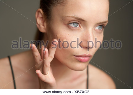 Young woman putting on makeup, close-up - Stock Photo