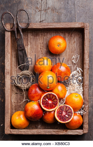 Ripe red oranges on textured wooden background - Stock Photo