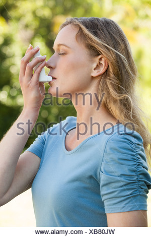 Young woman using asthma inhaler at park - Stock Photo
