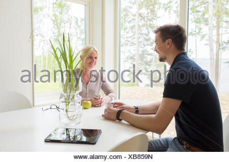 Sweden, Man and woman sitting and drinking at home - Stock Photo