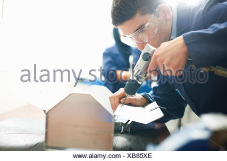Male student using hand drill in college workshop