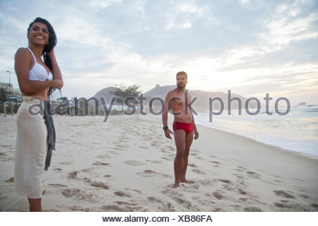 Mid adult couple standing on beach in swimwear - Stock Photo