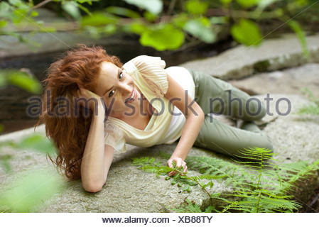 Young woman relaxing on rock - Stock Photo
