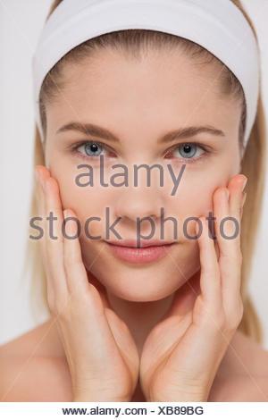 Portrait of a beautiful woman touching her cheeks - Stock Photo