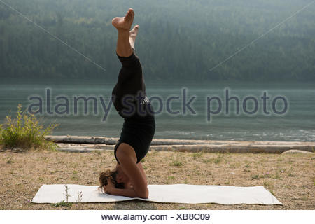 Sporty woman practicing head stand near the sea coast - Stock Photo