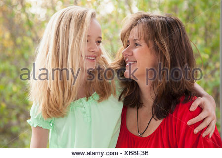 Girl hugging her mother and smiling, Bavaria, Germany - Stock Photo