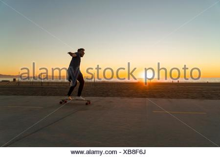 Young man using skateboard on pathway, beside beach, sunset - Stock Photo