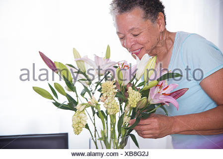 Senior woman smelling vase of flowers, smiling - Stock Photo