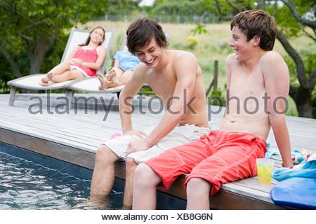 Teenage boys sat on the edge of a swimming pool - Stock Photo