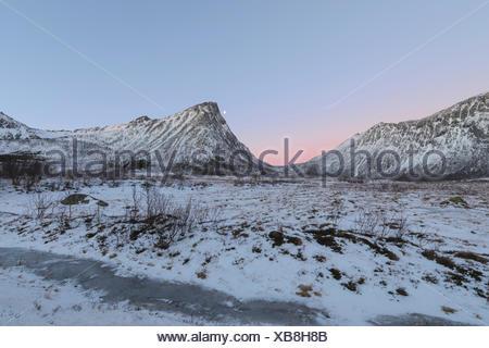 Pink sky at sunrise lights up the snowy peaks in the arctic winter Hamn i Senja Bergsfjordens Tromsø Norway Europe - Stock Photo