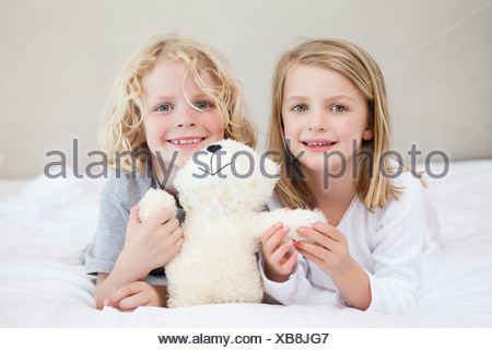 Siblings lying on the bed with teddy - Stock Photo