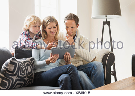 Parents and son using digital tablet - Stock Photo