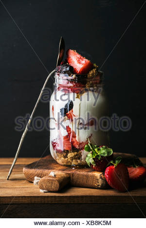 Yogurt oat granola with strawberries, mulberries, honey and mint leaves in tall glass jar on black backdrop - Stock Photo