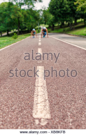 Young man and woman running in park - Stock Photo