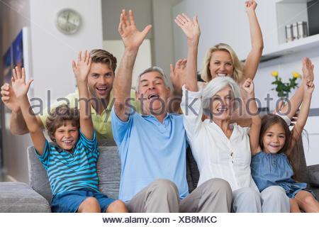 Multi-generation family raising their arms - Stock Photo
