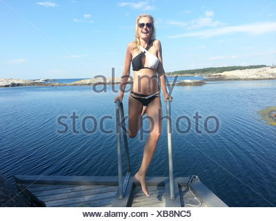 Woman messing about on jetty by fjord, Norway - Stock Photo